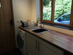 Woodpecker Annexe: the kitchen, showing the sink and the washing machine.